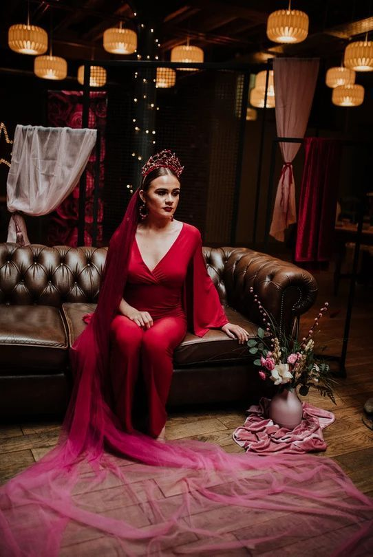 a deep red wedding jumpsuit, a jaw-dropping crown and earrings plus an ombre deep red to pink veil for a color-loving bride