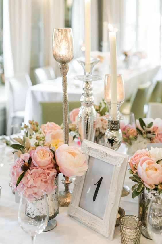 a fairy tale wedding tablescape with lots of blush and pink blooms, candles and mercury glass candleholders and vases is very elegant and chic