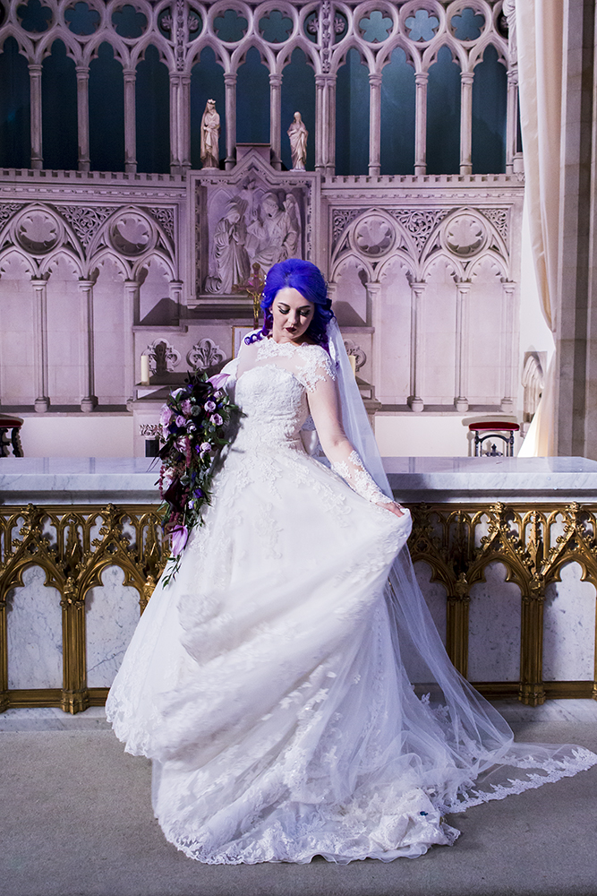 a gorgeous lace princess-style wedding gown with illusion sleeves and a neckline, a tain, purple hair and a dramatic bouquet