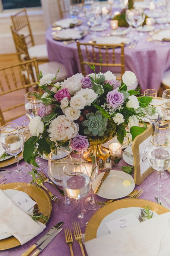 a lavender fairy tale wedding tablescape of white and lavender blooms, lavender tablecloth, succulents, gold chargers and cutlery