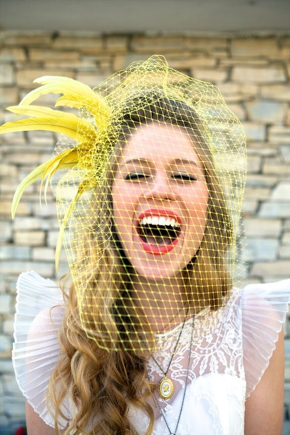 a retro wedding dress paired with a yellow birdcage veil with feathers for a bright and unusual touch