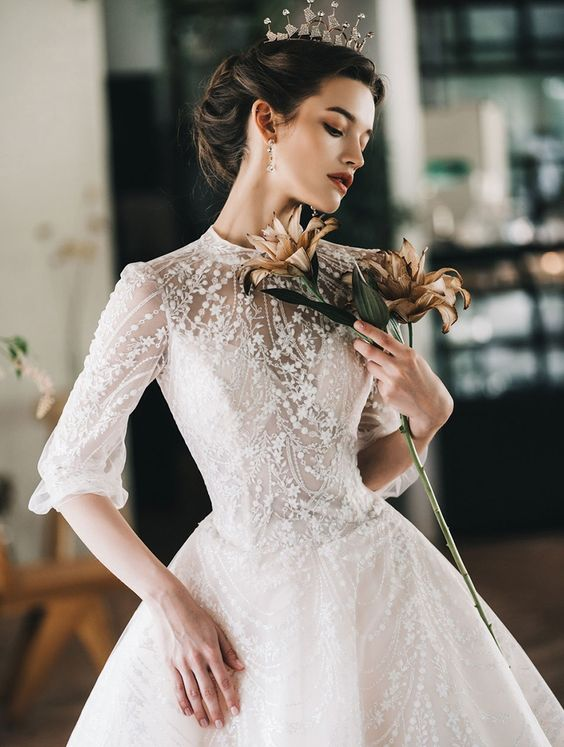 a jaw-dropping lace applique and embellished wedding ballgown with a high neckline and short sleeves plus a crown