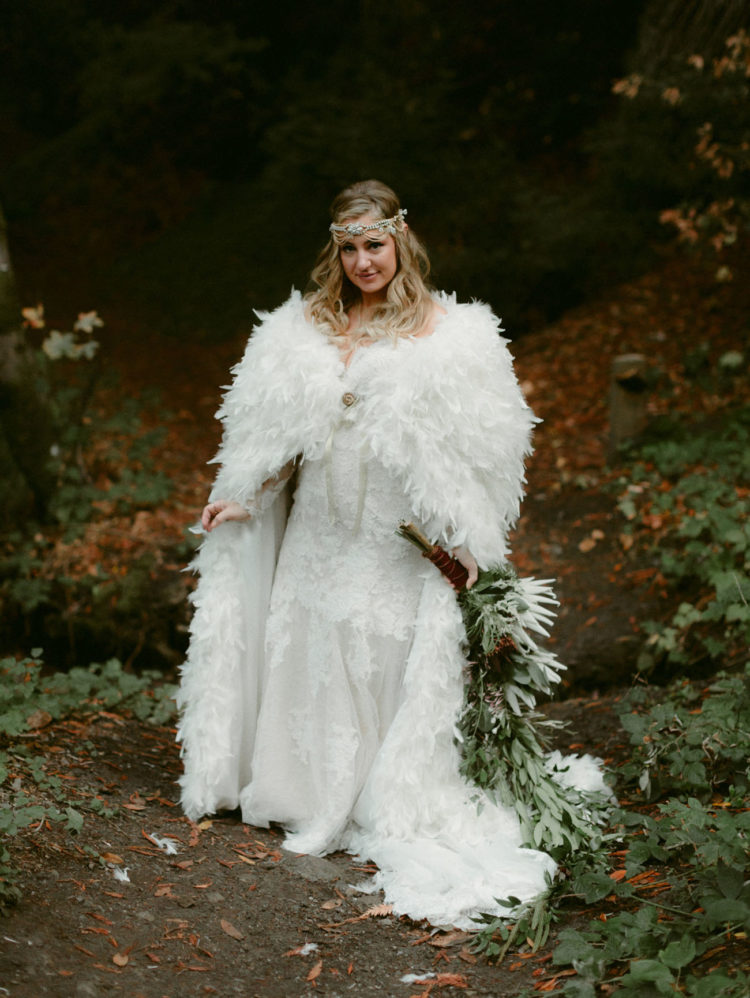 a lace sheath off the shoulder wedding dress with a train, a feather coverup, an embellished boho headpeice for a fairy tale bride