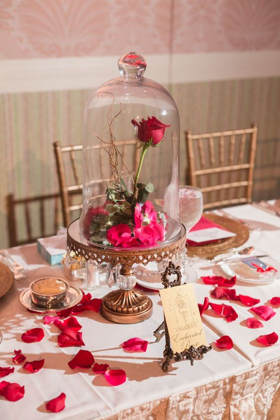 a refined fairy tale wedding centerpiece of a vintage cloche, bright petals, a rose, crystals and a vintage frame