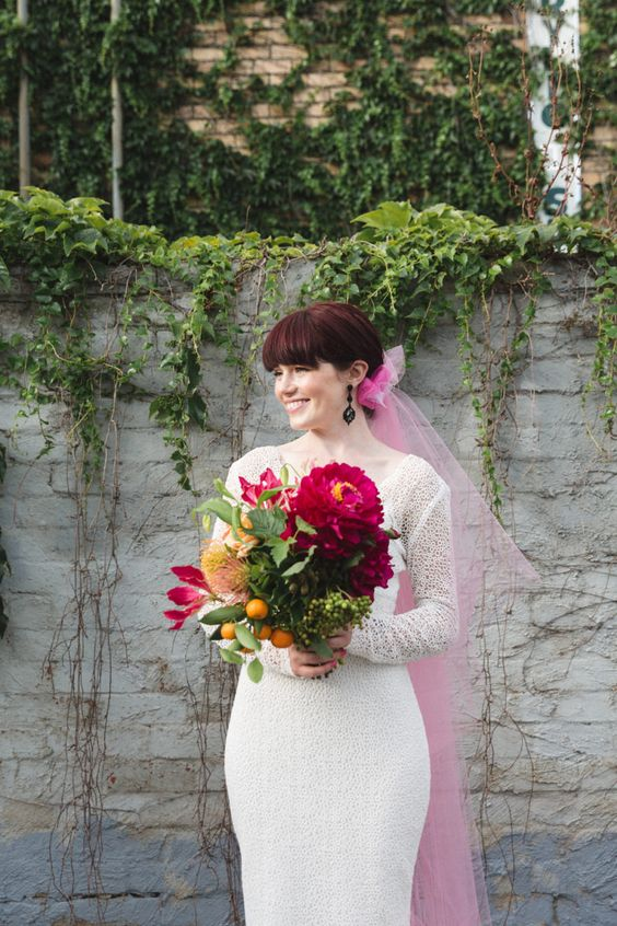 a white lace sheath wedding dress, black statement earrings and a pink veil for a bright and fun touch