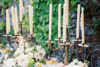 22 a romantic fairy tale wedding tablescape with blush and white blooms, greenery, candles in vintage candleholders and elegant glasses