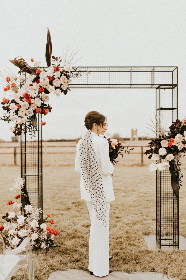 a white pantsuit paired with a black and white polka dot veil for a stylish 70s inspired look