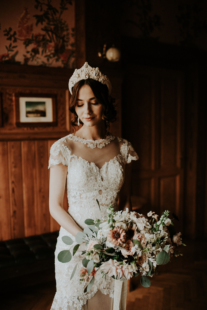 a romantic lace sheath wedding dress with an illusion neckline, cap sleeves and a sheer part in the skirt plus a statement headpiece