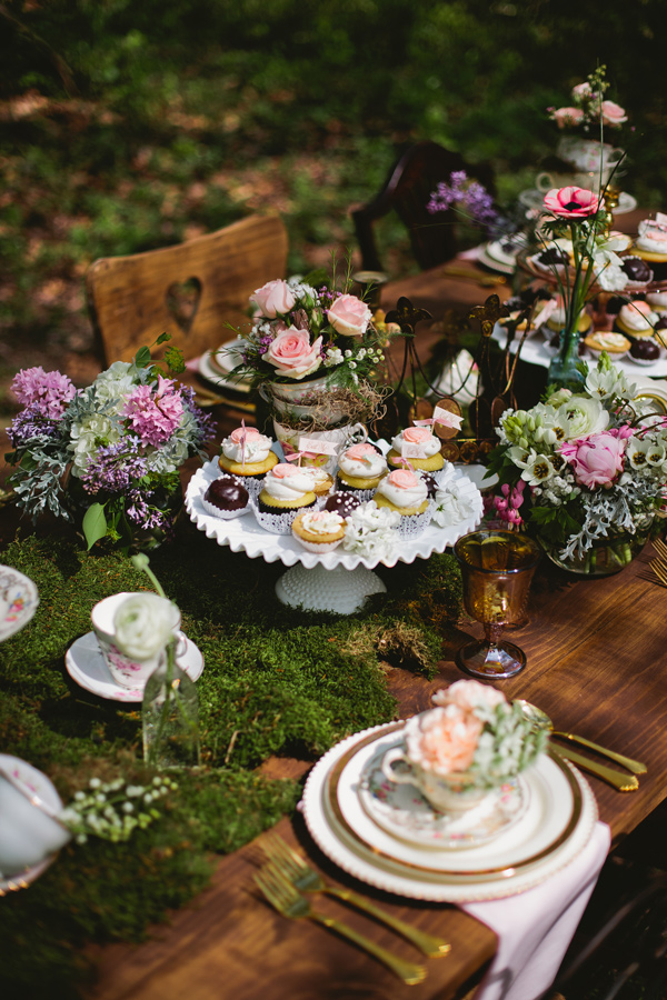 a romantic wedding tablescape with a moss runner, blush amd purple blooms, greenery, elegant porcelain and gold cutlery