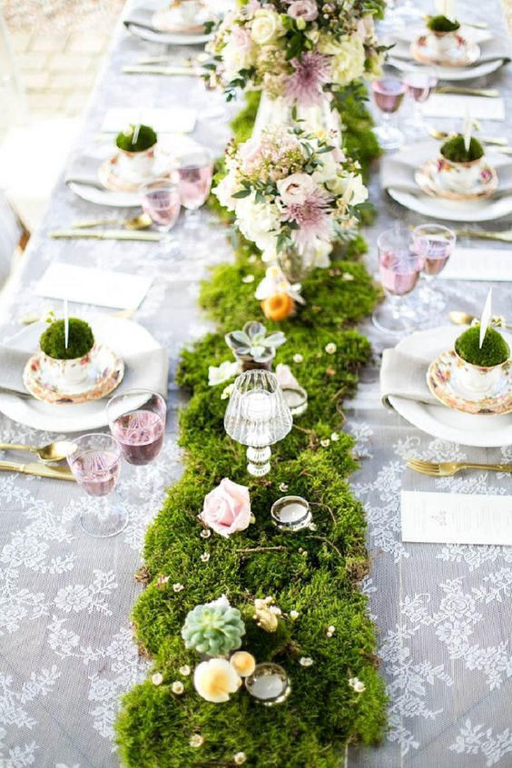 a spring fairy tale wedding tablescape with a grass runner with blush roses, crystals, candles, succulents and a lace tablecloth