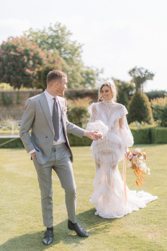 a unique mermaid lace ruffle wedding dress with sheer detailing, puff sleeves and a high neckline