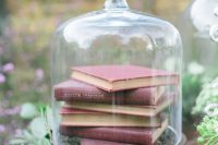 25 a wedding centerpiece of a vintage cloche with a stack of books and greenery is a lovely decor idea