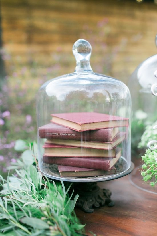 a wedding centerpiece of a vintage cloche with a stack of books and greenery is a lovely decor idea