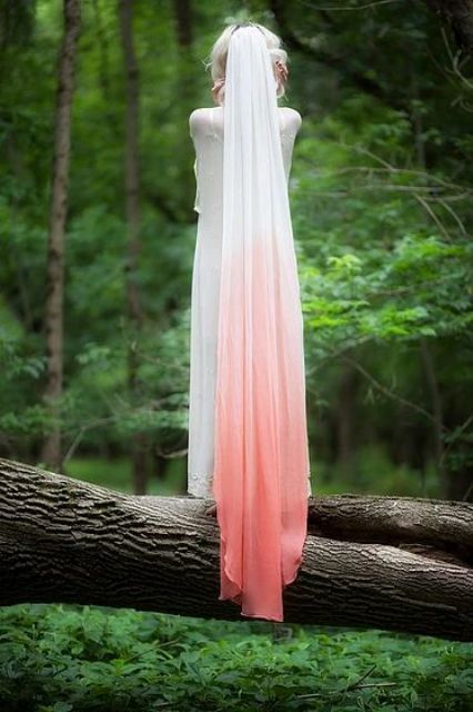 an ombre white to peachy pink veil makes a colorful statement and keeps your look unique