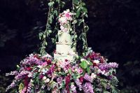 26 serve your wedding cake on a hanging piece with greenery, purple and pink blooms and top it with the same flowers