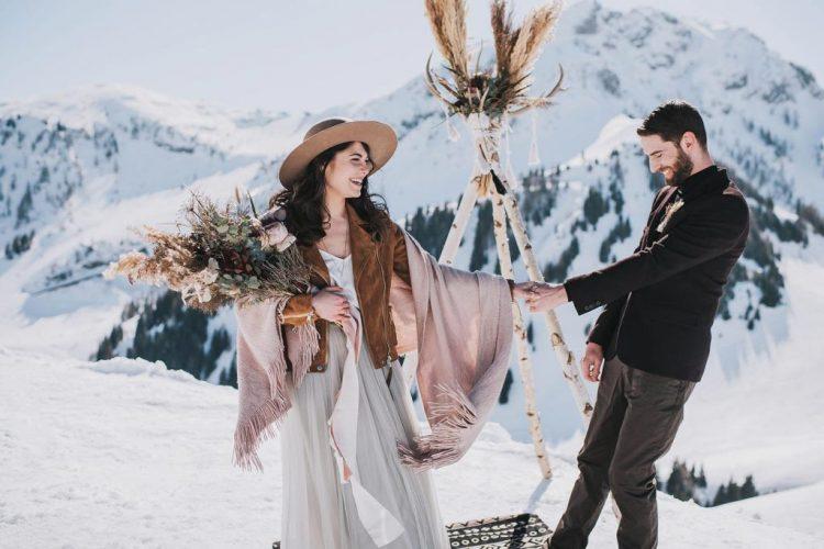 a black turtleneck, a black blazer, grey cargo pants and a dried grass boutonniere for a winter boho wedding