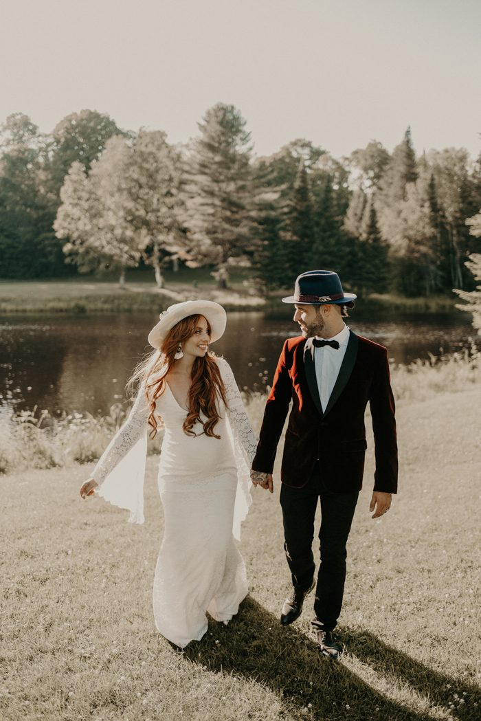 a burgundy velvet tux with black lapels, black pants and shoes, a navy hat and a bow tie for a refined boho look