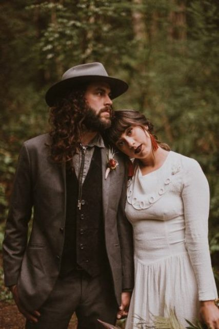 a grey suit, a black waistcoat, a grey shirt, a bolo tie and a hat plus a bold boutonniere for a winter boho look