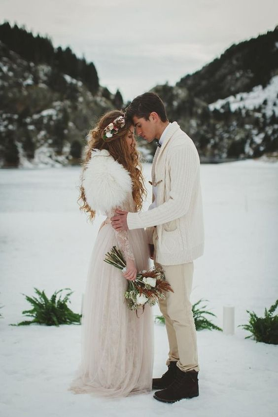 a groom rocking tan jeans, a white shirt, a white chunky cardigan and black boots for a winter boho wedding