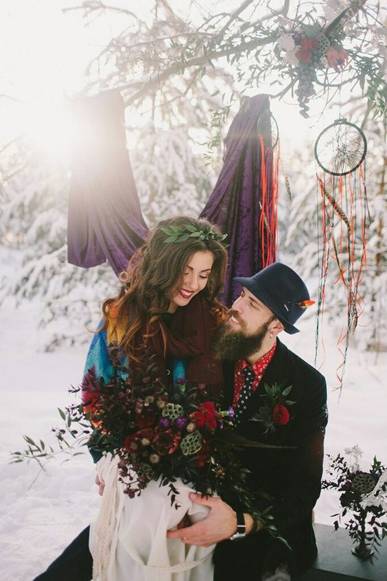 a printed red shirt, a printed black tie, a black suit and a navy hat with a bright feather for a winter woodland wedding