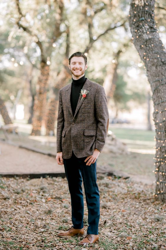 a simple boho winter groom look with a black turtleneck, a brown plaid blazer, navy pants, brown shoes and a bold boutonniere