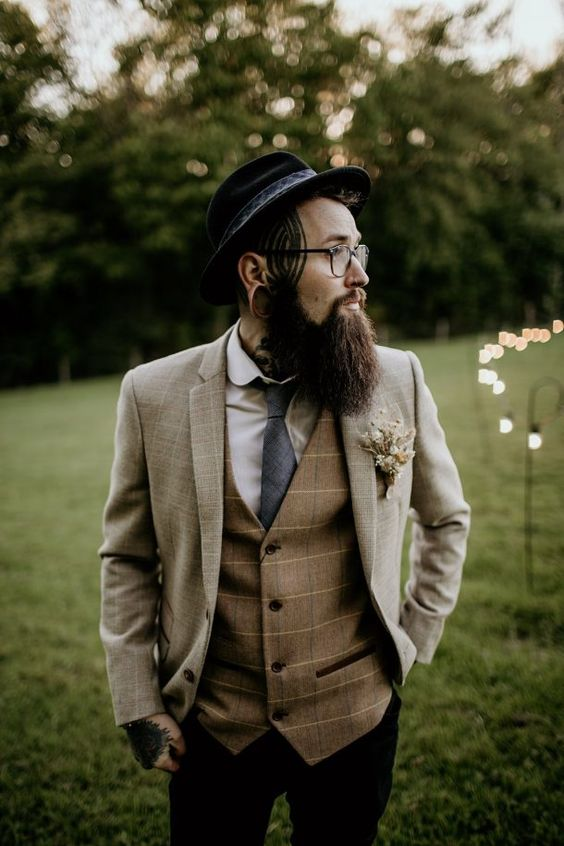a winter boho groom wearing black jeans, a creamy plaid blazer, a matching brown waistcoat, a white shirt, a grey tie and a black hat