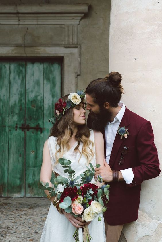 tan pants, a white shirt, a deep purple oversized blazer, a thistle boutonniere plus a man bun for a fall or winter boho look
