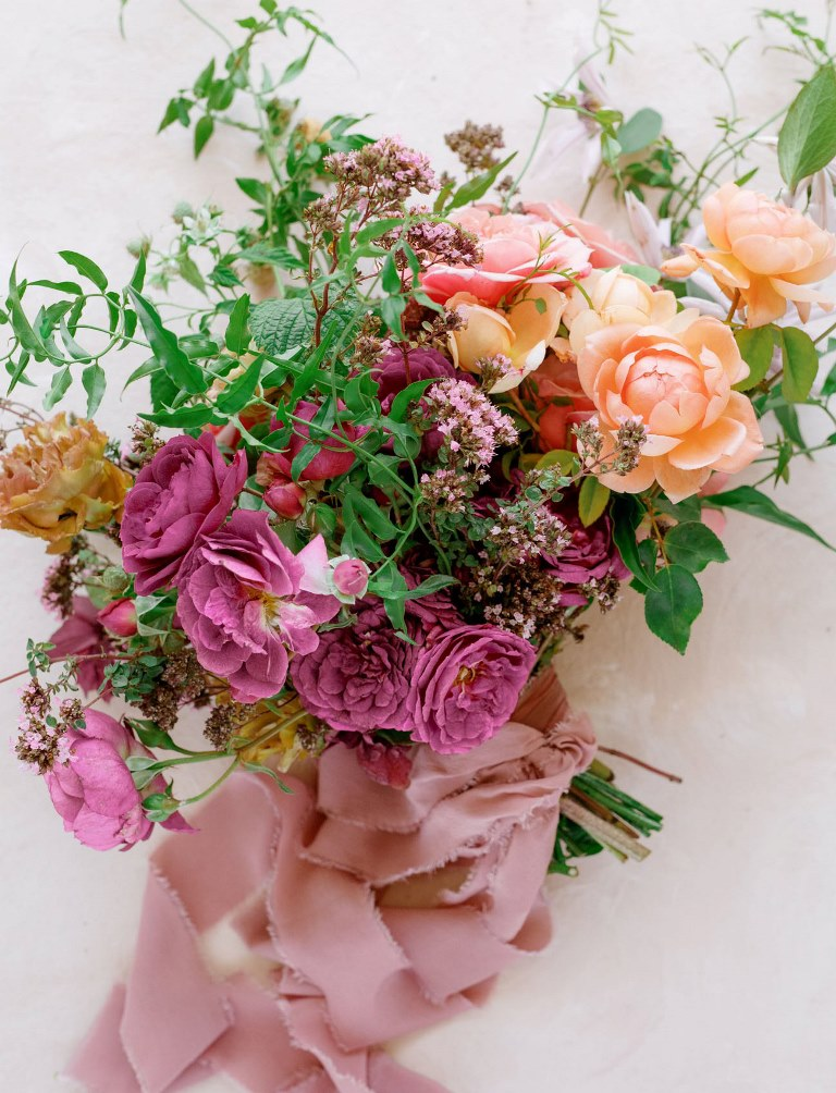 The weding bouquet was done with bold blooms, greenery and pink ribbons