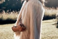 02 a blush fuzzy fur coat over a lace wedding dress to add a bit of edge to a romantic and glam bridal look