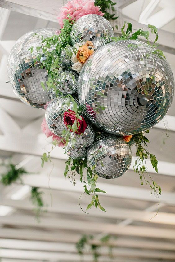 a bold wedding decoration of disco balls, bright blooms and greenery is a stylish and cool idea to rock