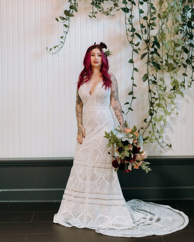 One bride was wearing a boho lace A-line wedding dress with a deep neckline and a train