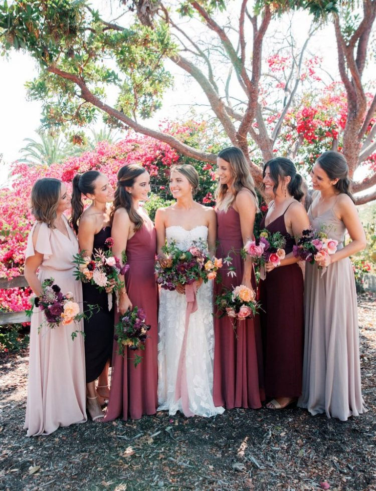 The bride was wearing a strapless floral wedding dress, the bridesmaids were rocking berry-hued dresses