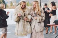 03 a bride wearing a neutral faux fur coat over a romantic lace wedidng dress and a beautiful floral crown