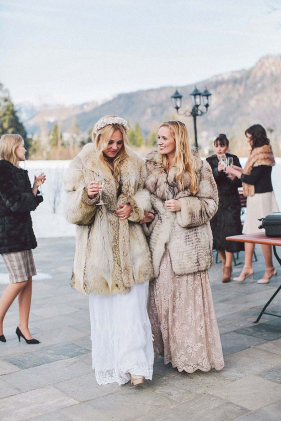 a bride wearing a neutral faux fur coat over a romantic lace wedidng dress and a beautiful floral crown