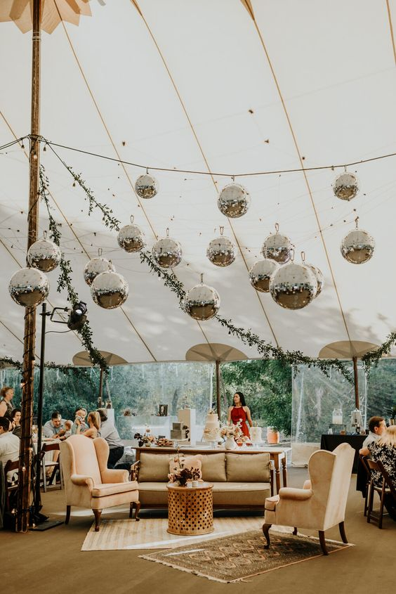 a cozy wedding lounge with lots of disco balls hanging over it that bring a cool party feel to the space