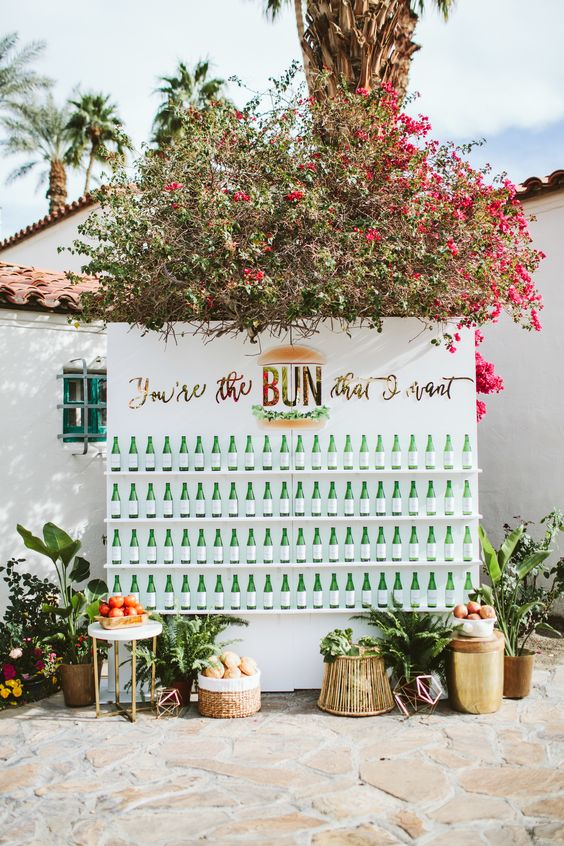 a bright drink wall with flowers over it, fruits and tropical plants and bottles on the shelves