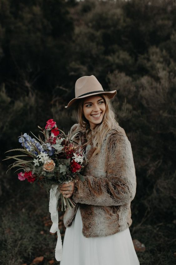 a brown faux fur bridal coat and a neutral hat are a nice idea for a fall or winter boho bride