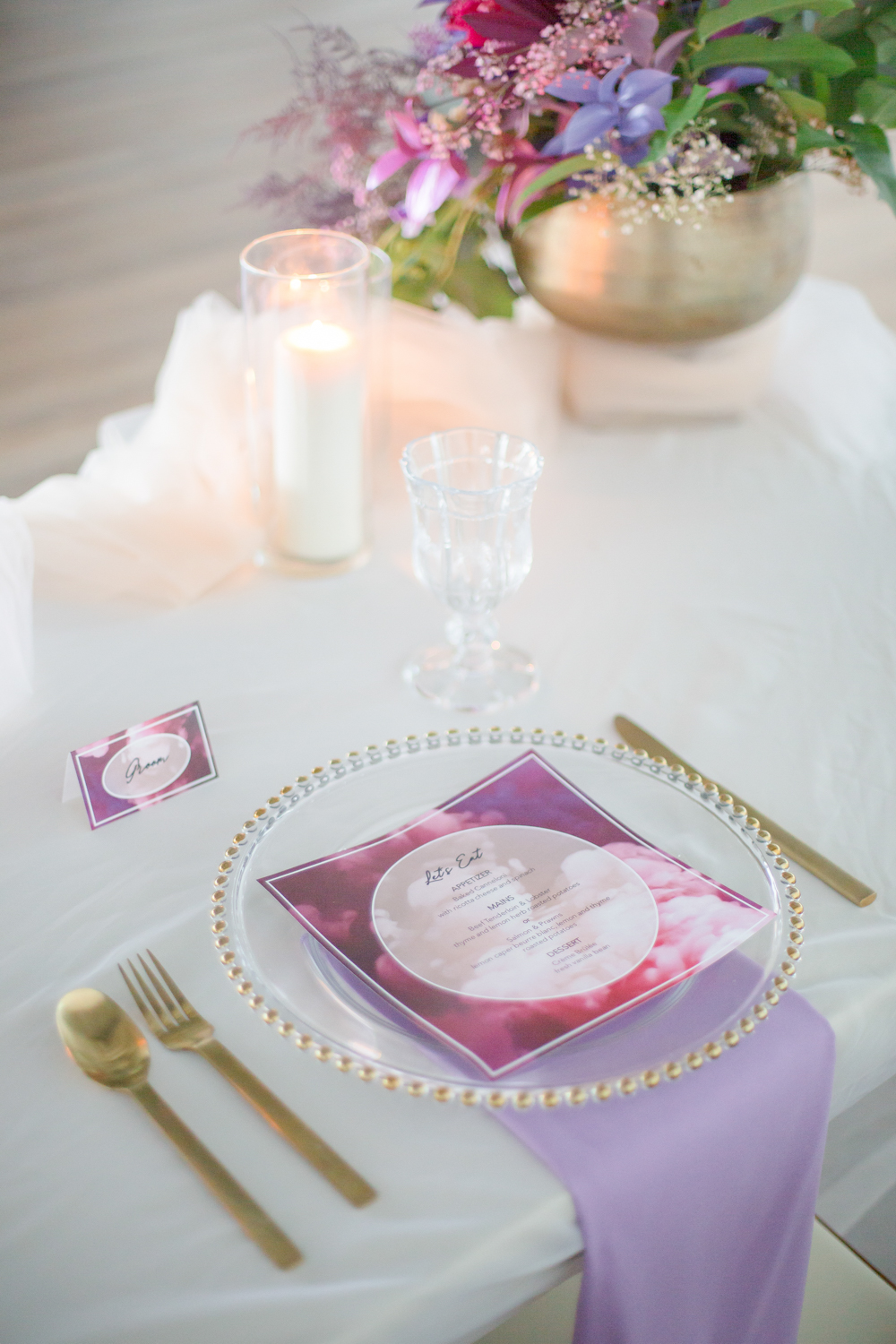 The wedding tablescape itself was simple, with a blush runner, candles, a sheer charger and gold cutlery , yet bright linens