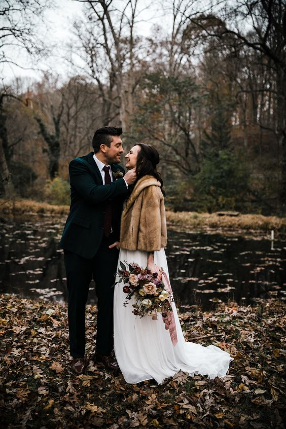 a brown faux fur short coat over a white wedding dress for a slight touch of color and a cozy feel outside