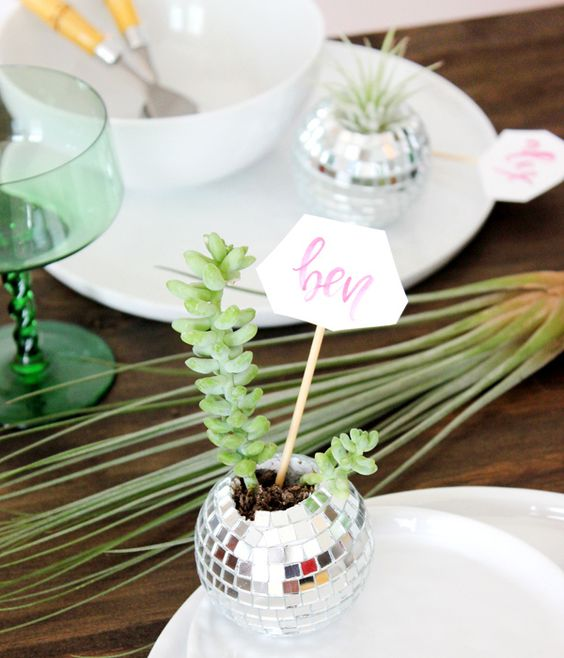 a disco ball planter with succulents and a place card will be a nice solution for a wedding or party tablescape