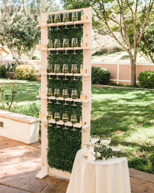 a wooden champagne wall with boxwood looks chic and trendy