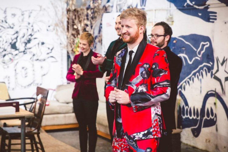 The groom's second look was done with a bold red suit printed with birds and flowers