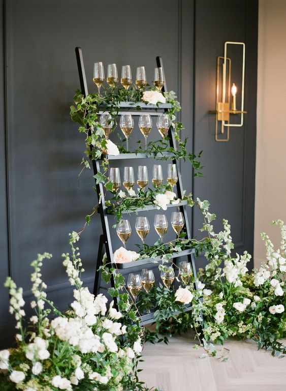 a black stand with lots of lush greenery and white blooms plus drinks in glasses is very chic and romantic
