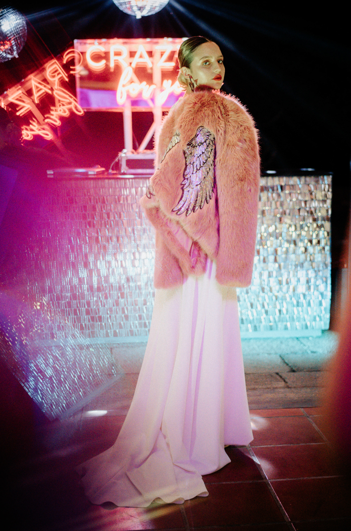 a whimsical pink faux fur coat with embroidred iridescent angel wings is a fantastic and breathtaking piece to wear