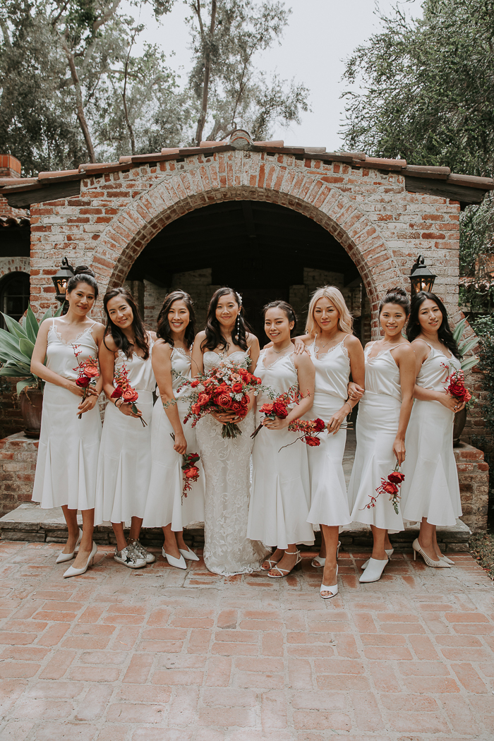 The bridesmaids were wearing white midi dresses with lace detailing and mismatching shoes