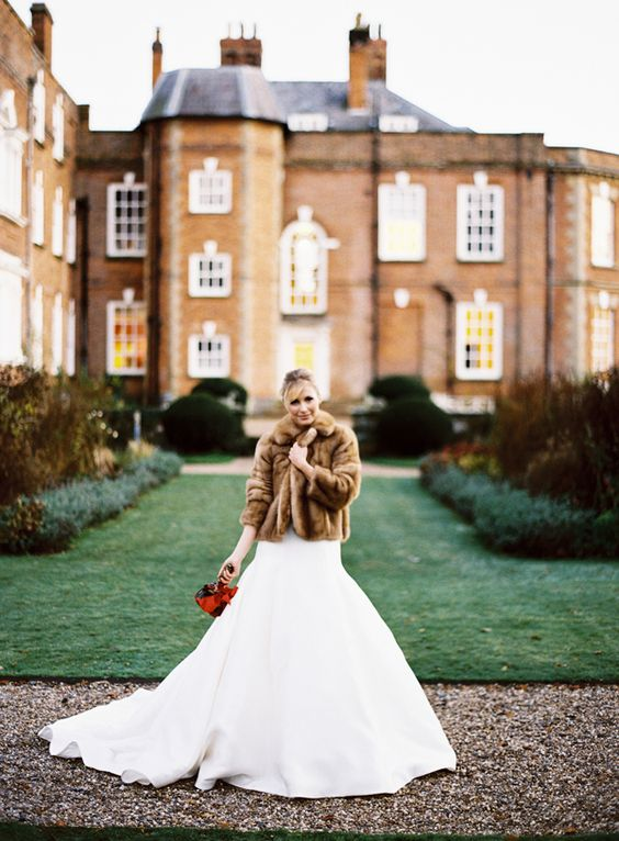 a classic brown faux fur coat over a mermaid wedding dress adds color and a luxurious feel to the outfir