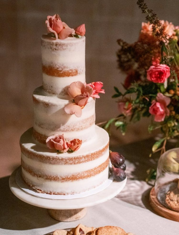 The wedding cake was a naked one, with pink blooms and fruits