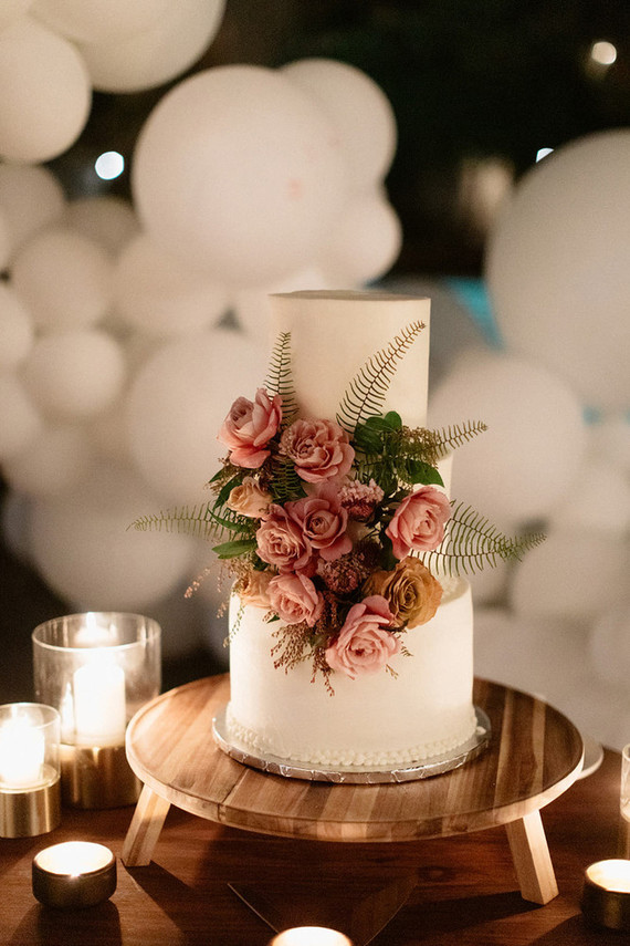 The wedding cake was a white one, with ferns, leaves and pink and mauve blooms