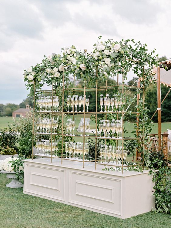 a beautiful drink stand of a white base and metal and glass shelves, lush greenery and white blooms is refined