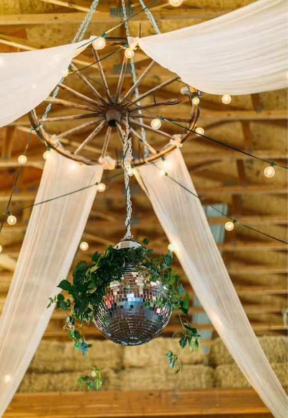 a rustic wedding chandelier of an old wheel, lights, some sheer fabric and a disco ball decorated with greenery